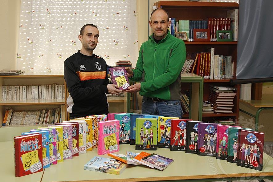 El presidente del Racing Cuéllar, Jesús Ángel Ferreiro (izquierda) entrega los libros al director del colegio La Villa, Álvaro Catalina. Foto: Gabriel Gómez
